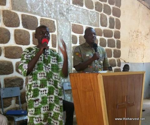 Pastor Salif preaching and Pastor Justin