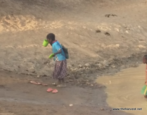 This little girl drinking the nasty water.